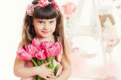 Portrait of a beautiful little girl with flowers Stock Photos