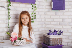 Portrait of a beautiful little girl with flowers. Sitting at the table. Little girl sits in front of a white brick wall in the studio. Textured brick background Royalty Free Stock Photography