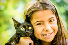 Portrait of a beautiful little girl holding a black cat Stock Photography