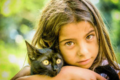 Portrait of a beautiful little girl holding a black cat Stock Photo