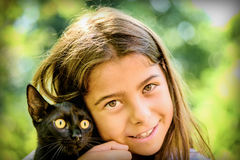 Portrait of a beautiful little girl holding a black cat Royalty Free Stock Image