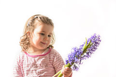 Portrait of a beautiful little girl holding flowers. Close up portrait of a beautiful little girl with bouquet of bluebells in one hand. Little girl looking at Stock Photos