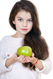 Portrait of a beautiful little girl holding a green apple. Isolated on white background Stock Photo