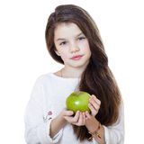 Portrait of a beautiful little girl holding a green apple Royalty Free Stock Photography