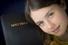Portrait of beautiful little girl holding Holy Bible Stock Photos