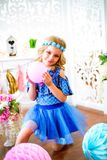 A portrait of a beautiful little girl in a studio decorated many color balloons. A portrait of a beautiful little girl laughs in a studio decorated many color Stock Photos