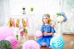 A portrait of a beautiful little girl in a studio decorated many color balloons. A portrait of a beautiful little girl laughs in a studio decorated many color Royalty Free Stock Photos