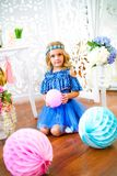 A portrait of a beautiful little girl in a studio decorated many color balloons. A portrait of a beautiful little girl laughs in a studio decorated many color Stock Images