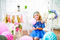 A portrait of a beautiful little girl laughs in a studio. Decorated many color balloons Stock Photography