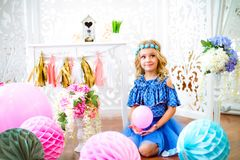A portrait of a beautiful little girl laughs in a studio. Decorated many color balloons Royalty Free Stock Photos