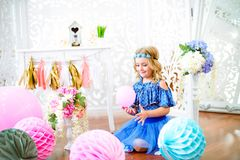 A portrait of a beautiful little girl laughs in a studio. Decorated many color balloons Royalty Free Stock Photography