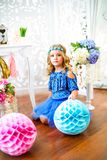 A portrait of a beautiful little girl laughs in a studio. Decorated many color balloons Royalty Free Stock Images