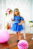 A portrait of a beautiful little girl laughs in a studio. Decorated many color balloons Royalty Free Stock Photo