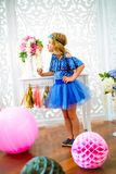 A portrait of a beautiful little girl laughs in a studio. Decorated many color balloons Royalty Free Stock Image