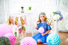 A portrait of a beautiful little girl laughs in a studio. Decorated many color balloons Stock Images