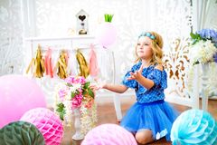 A portrait of a beautiful little girl laughs in a studio. Decorated many color balloons Stock Image