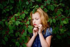 Portrait of beautiful little girl of leaves cherries Stock Photography