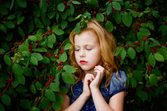 Portrait of beautiful little girl of leaves cherries Stock Image