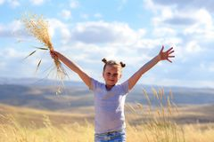 Portrait Of A Beautiful Little Girl In The Middle Of A Wheat Field. stock photo