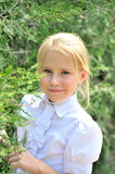 Portrait of the beautiful little girl in a park. Portrait of the beautiful little blonde girl in a park near thuyas Stock Photography