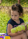 Portrait of a beautiful little girl. Little girl playing with her doll Royalty Free Stock Photo
