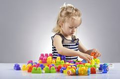 Portrait of beautiful little girl playing with plastic toy cubes Royalty Free Stock Photos