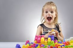 Portrait of beautiful little girl playing with plastic toy cubes Stock Images
