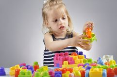 Portrait of beautiful little girl playing with plastic toy cubes Royalty Free Stock Images