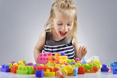 Portrait of beautiful little girl playing with plastic toy cubes Stock Image