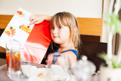 Portrait of a beautiful little girl at the restaurant Stock Image