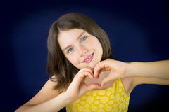 Portrait of beautiful little girl showing heart shape with her h Royalty Free Stock Photography