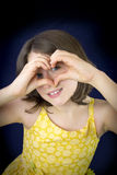 Portrait of beautiful little girl showing heart shape with her h Stock Photography