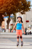 Portrait of beautiful little girl stands on roller skates in a city park in warm sunshiny summer day. Sportive little girl dressed in the colorful sportwear Royalty Free Stock Image