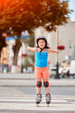 Portrait of beautiful little girl stands on roller skates in a city park in warm sunshiny summer day. Sportive little girl dressed in the colorful sportwear Royalty Free Stock Photography