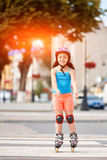 Portrait of beautiful little girl stands on roller skates in a city park in warm sunshiny summer day. Sportive little girl dressed in the colorful sportwear Stock Photos