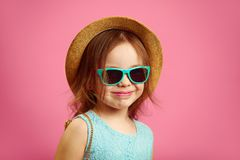 Portrait of beautiful little girl with straw hat and sunglasses, wears blue dress, stands on pink isolated. royalty free stock photography