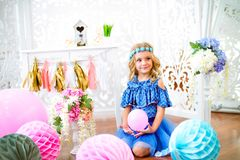 A portrait of a beautiful little girl in a studio decorated many color balloons. A portrait of a beautiful little girl laughs in a studio decorated many color Royalty Free Stock Images