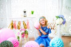 A portrait of a beautiful little girl in a studio decorated many color balloons. A portrait of a beautiful little girl laughs in a studio decorated many color Stock Photography