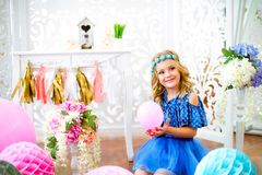A portrait of a beautiful little girl in a studio decorated many color balloons. A portrait of a beautiful little girl laughs in a studio decorated many color Stock Photo