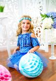 A portrait of a beautiful little girl in a studio decorated many color balloons. A portrait of a beautiful little girl laughs in a studio decorated many color Royalty Free Stock Image