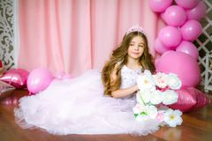 A portrait of a beautiful little girl in a studio decorated many color balloons. A portrait of a beautiful little girl laughs in a studio decorated many color Stock Image