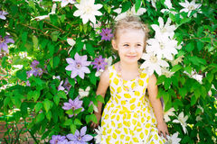 Portrait of a beautiful little girl in summer dress, clematis fl Royalty Free Stock Image