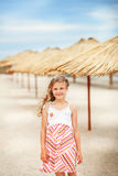 Portrait of a beautiful little girl in a sundress standing on a Royalty Free Stock Photo
