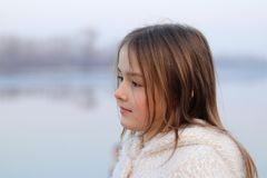 Portrait of beautiful little girl in white coat looking thoughtfully on the left. Outdoors Royalty Free Stock Photography