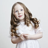 Portrait of a beautiful little girl in a white dress and veil on Royalty Free Stock Images