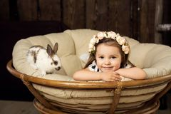 Portrait of a beautiful little girl in a wreath of flowers. A girl with a cute fluffy white Easter bunny stock photography