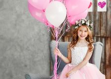 Portrait a beautiful little girl in a wreath of fresh flowers and an elegant pink dress celebrates her birthday in a white studio stock photos