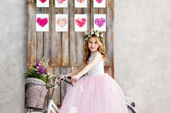 Portrait of a beautiful little girl in a wreath of fresh flowers on her head sits on a bike in a lush pink dress. Happy childhood stock photo