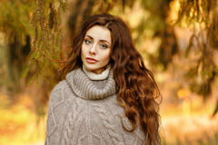 Portrait of a beautiful and a little sad girl with long wavy hai. R in knit sweater autumn at sunset Stock Photo