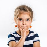 Portrait of a beautiful little thoughtful girl. Child close up. Photo on a light background Royalty Free Stock Photo